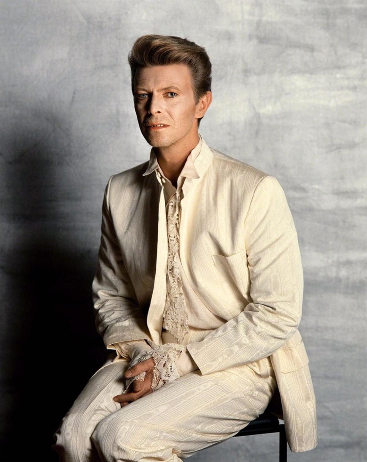 Mężczyzna siedzący na stołku w białym garniturze