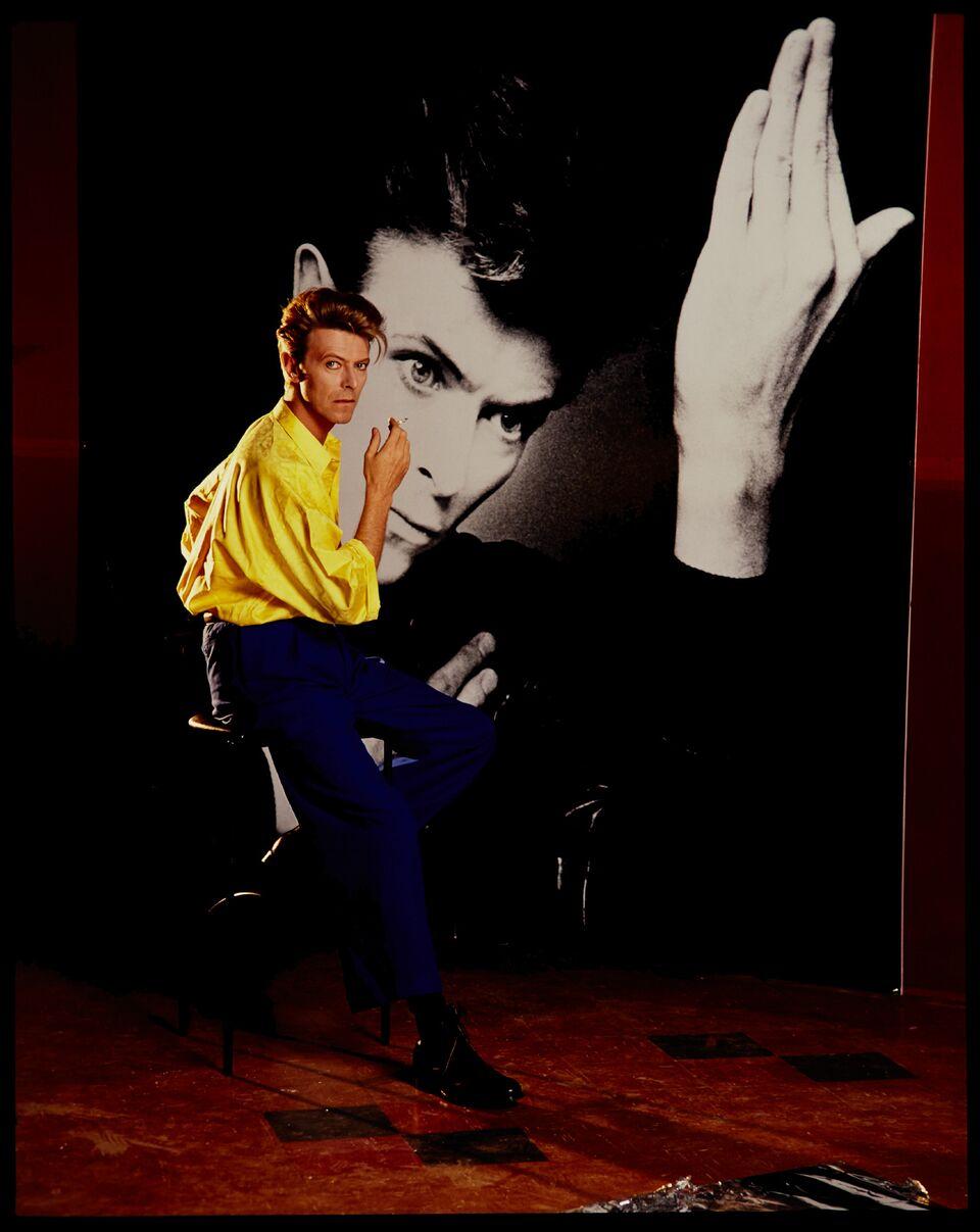 Mężczyzna w żółtej koszuli i niebieskich spodniach siedzi na stołku