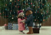 Dwa pluszowe niedźwiadki przytulające się na tle choinki