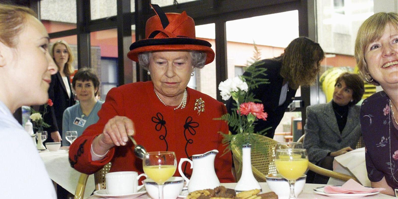 Starsza kobieta ubrana w czerwoną suknię je śniadanie.