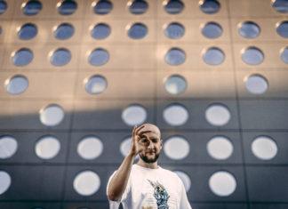 Mężczyzna w czapce i koszulce stojący na tle dziurawej ściany