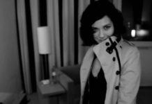 Czarno-białe zdjęcie kobiety ubranej w płaszcz