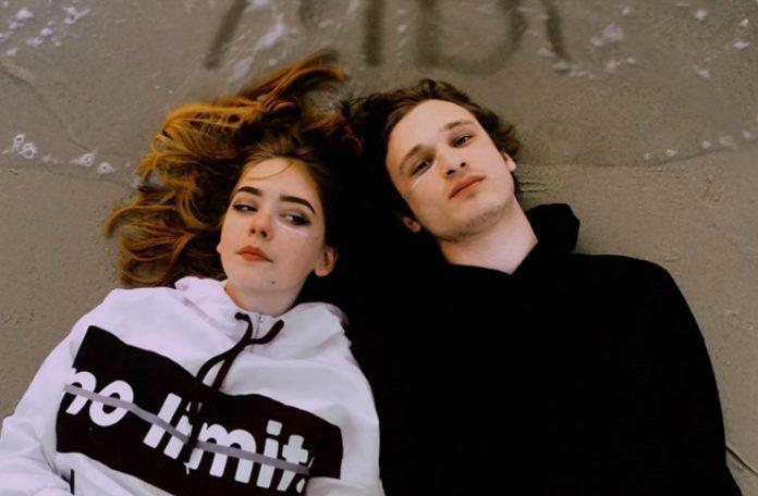 Chłopak i dziewczyna leżący nad brzegiem morza