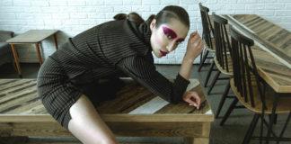 Dziewczyna z mocno umalowanymi oczami leżąca na stole