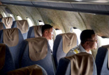 Wnętrze samolotu z brudynymi fotelami i dwójką ludzi