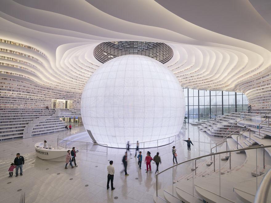 Białe, ogromne wnętrze biblioteki z wielką świetlną kulą na środku