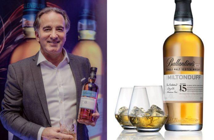 Mężczyzna trzymający butelkę whiskey i obok butelka whiskey ze szklankami