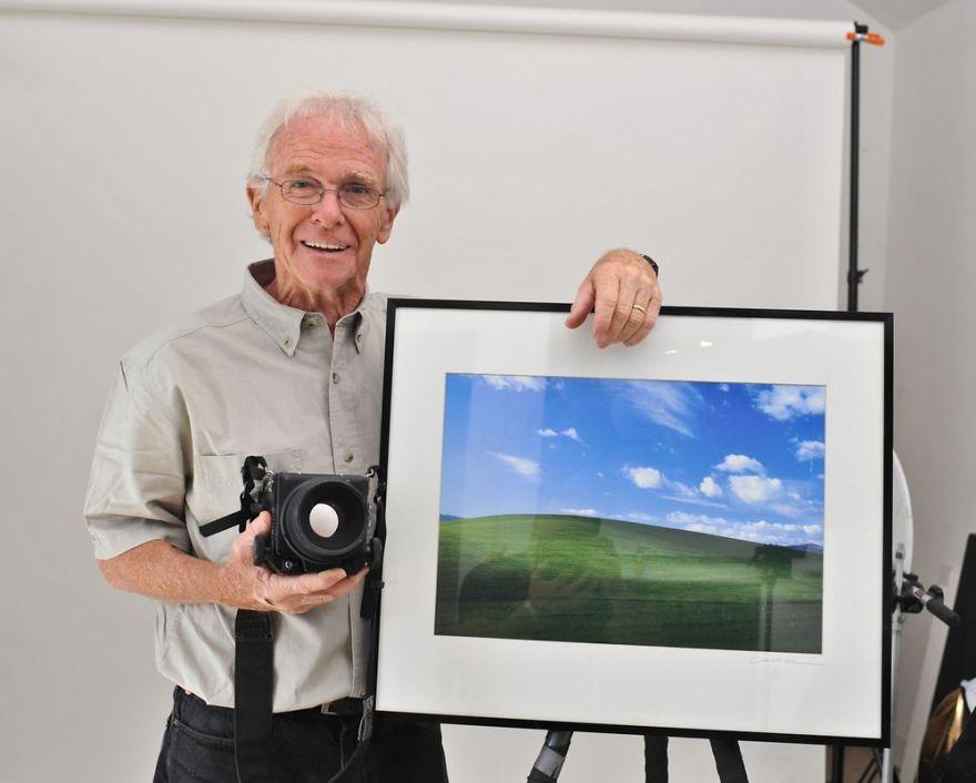 Starszy mężczyzna stojący ze zdjęciem łąki