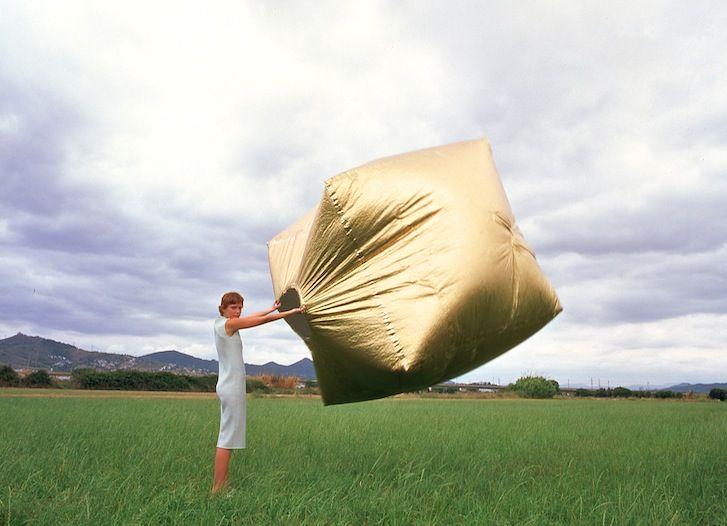 Kobieta trzymająca w powietrzu dużą, złotą kostkę wypełnioną powietrzem