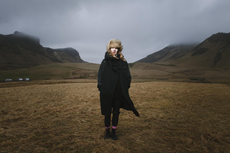 Kobieta stoi na tle gór i łąk.