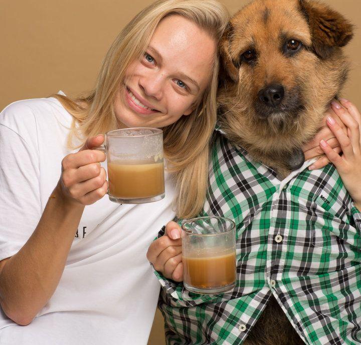 Kobieta trzymająca kawę przytula się do psa.