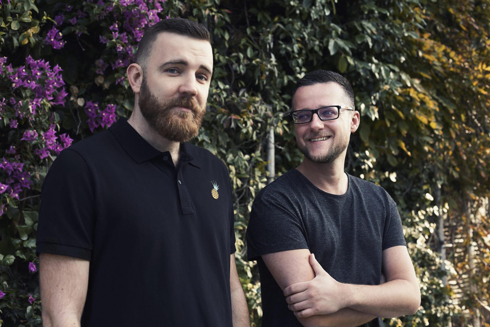 Dwóch mężczyzn na tle zielonych krzaków
