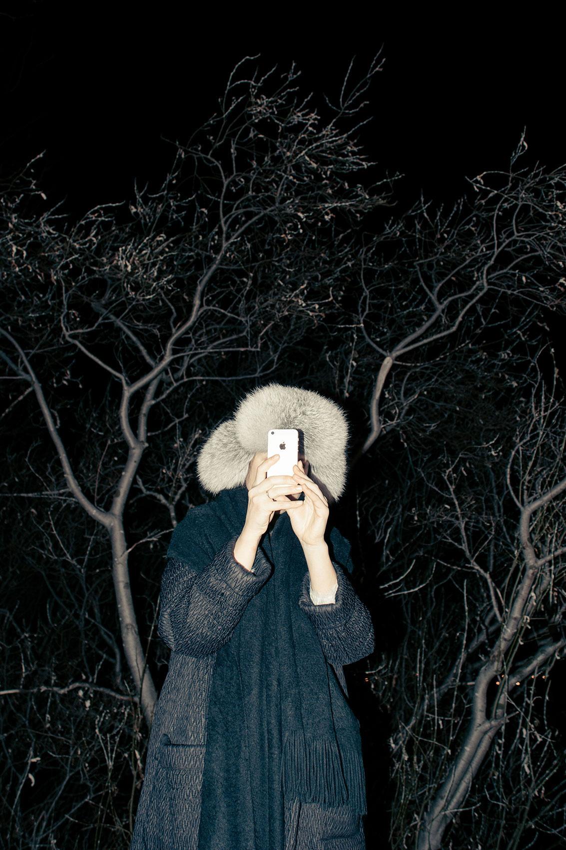 Kobieta w ciemnościach trzyma telefon przy twarzy.