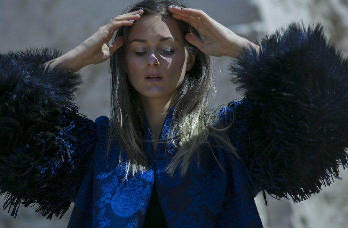 Dziewczyna ubrana w niebieską kurtkę trzymająca dłonie na wysokości skroni