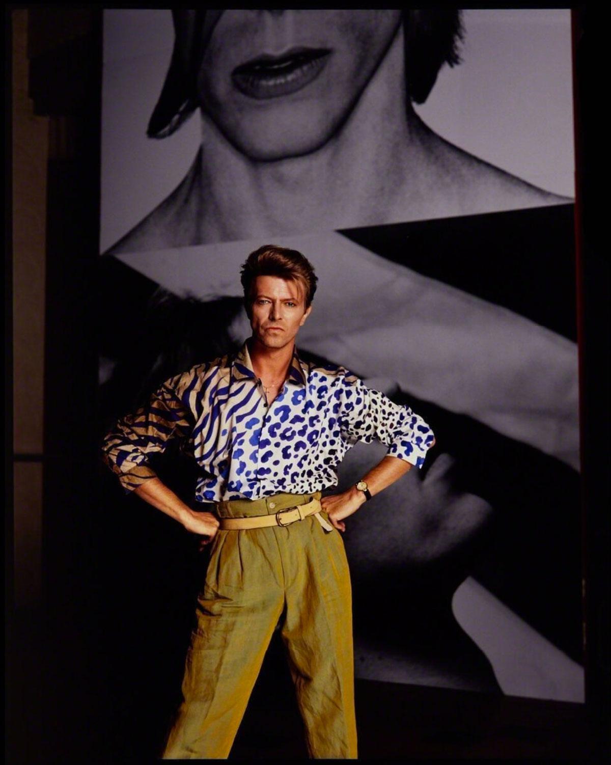 Mężczyzna z rękami podpierającymi boki stoi przy ścianie