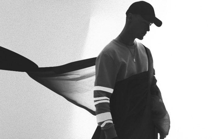 Czarno-biała fotografia przedstawiająca mężczyzne stojąceog profilem