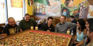 Wielka pizza i ludzie siedzący dookoła niej