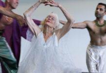 Stara tancerka tańczy z rękami uniesinymi w górze i zamkniętymi oczami. Ma na sobie białą, zwiewną suknię. Za nią tańczy dóch mężczyzn. Jeden ma na sobie fioletowe kimono, drugi jest bez koszulki, w białych spodniach.