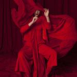Dziewczyna zakryta czerwonym materiałem, na czerwonym tle