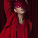 Dziewczyna w czerwonym stroju na tle czerwonej zasłony