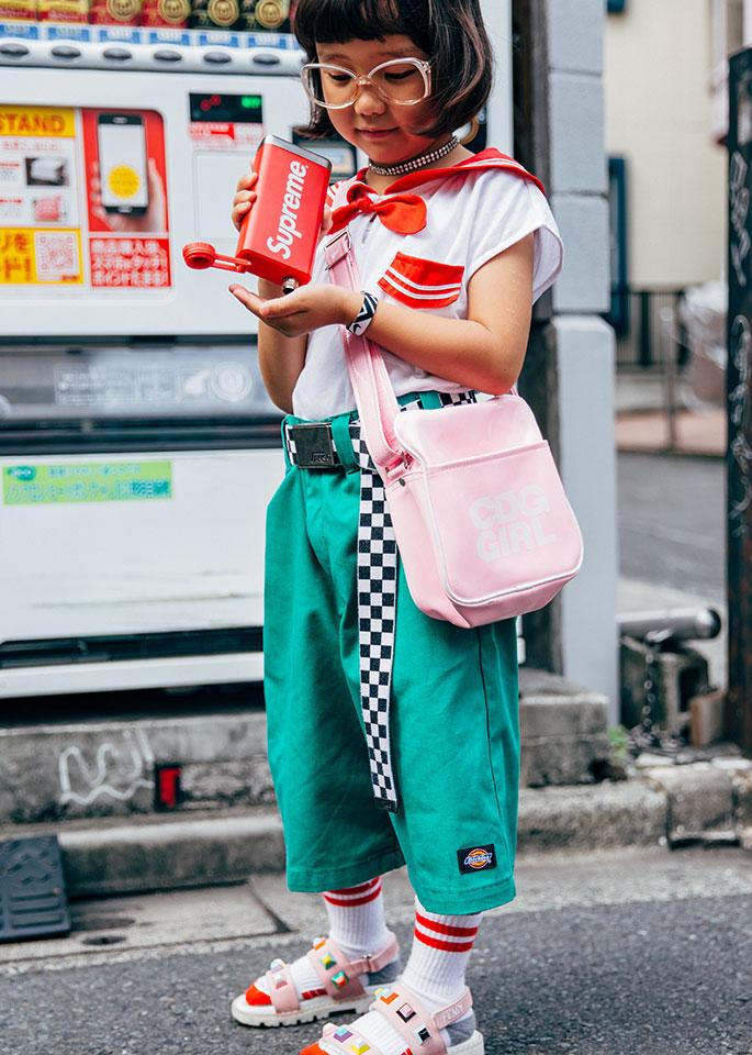 Azjatycka dziewczynka stojąca na ulicy w turkusowych spodniach i białej koszulce