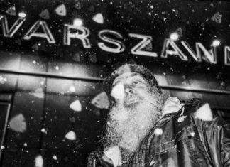 Czarno-białe zdjęcie przedstawiające siwego mężczyzne na tle napisu Warszawa