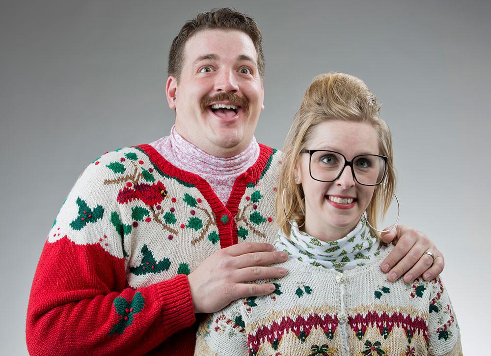 Kobieta i mężczyzna są przebrani w brzydkie świąteczne swetry.