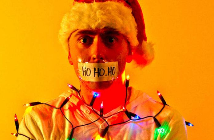 Mężczyzna w czapce Mikołaja z zaklejonymi ustami i obwiązany świątecznymi lampkami
