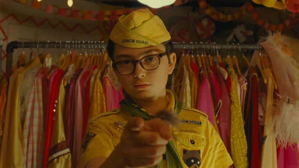 Chłopiec w okularach wskazuje w obiektyw palcem.