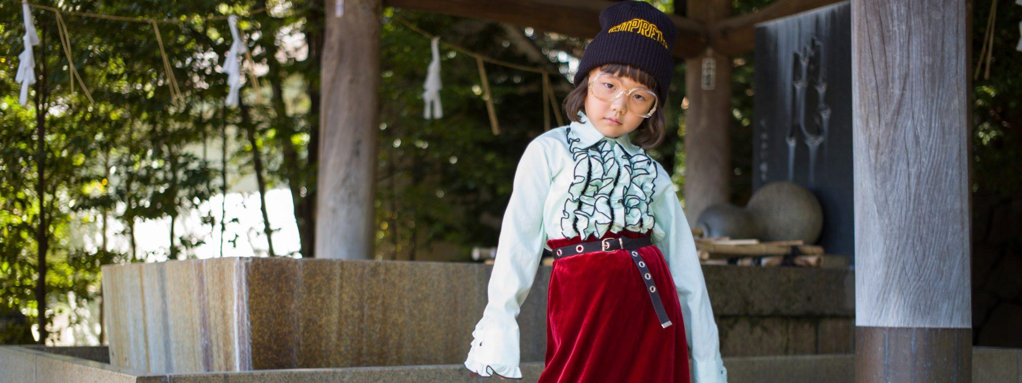 Azjatyckie dziecko stojące w czerwonej spódnicy i białej koszuli