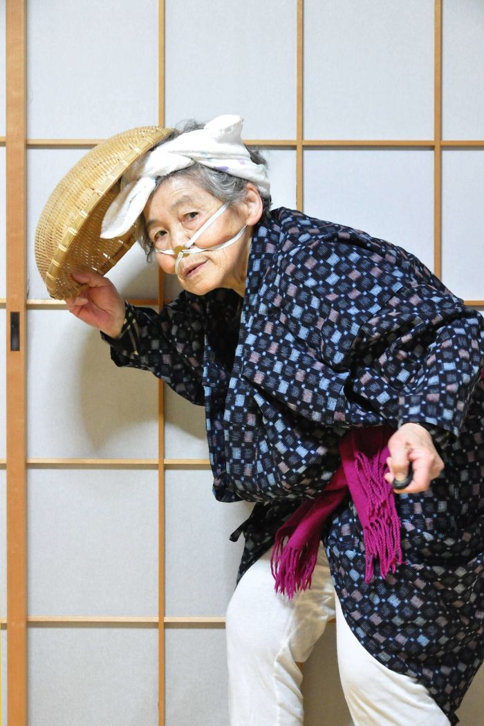 Starsza kobieta ubrana w kimono z czymś dziwnym na głowie