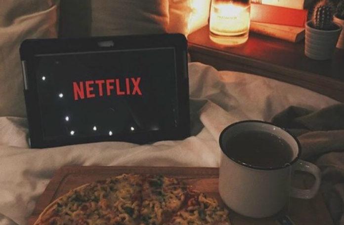 Tablet z włączonym Netflixem leżący na łózku