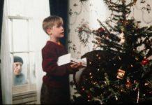 Kadr z filmu kevin sam w domu blond chlopiec w czerwonym swetrze i granatowych spodniach trzyma pudelko w rekach i bokiem stoi przy choince swiatecznej za oknem stoi zloczynca