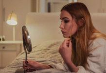 Dziewczyna leżąca na łóżku, patrzy w lusterko