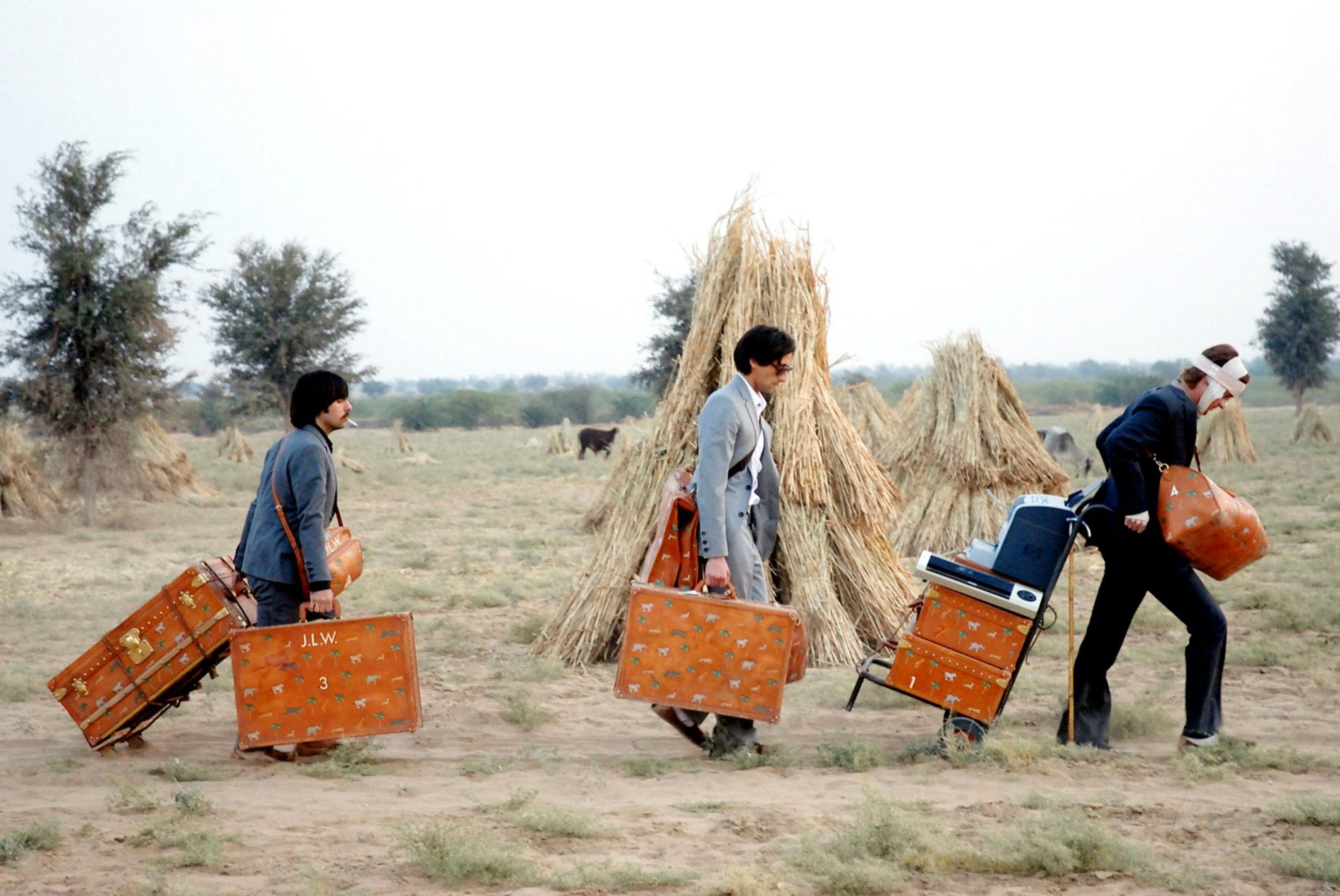 Trzech mężczyzn idzie po polanie.