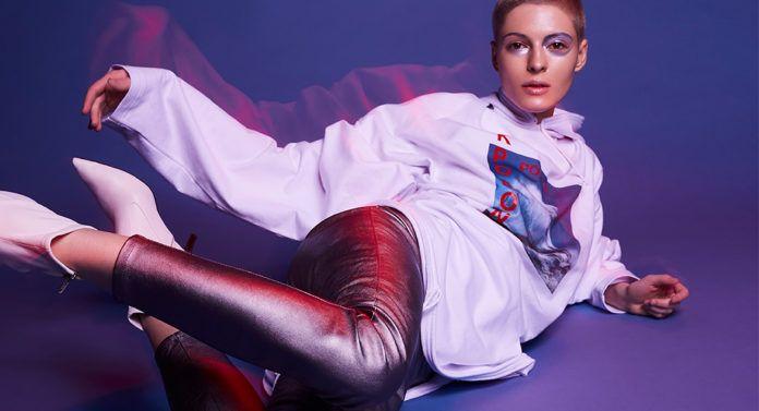 Dziewczyna w białej bluzie i metalicznych spodniach leżąca na niebieskim tle