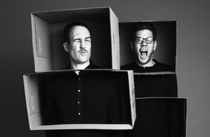 Dwóch mężczyzn ubranych na czarno z kartonami na głowach