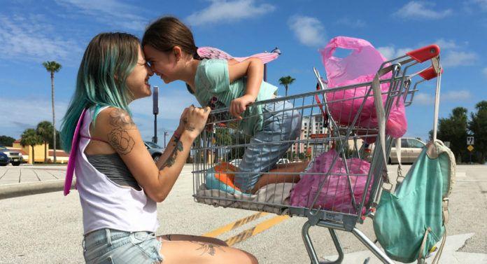 Mała dziewczynka w wózku sklepowym i kucająca przy nim dziewczyna z kolorowymi włosami