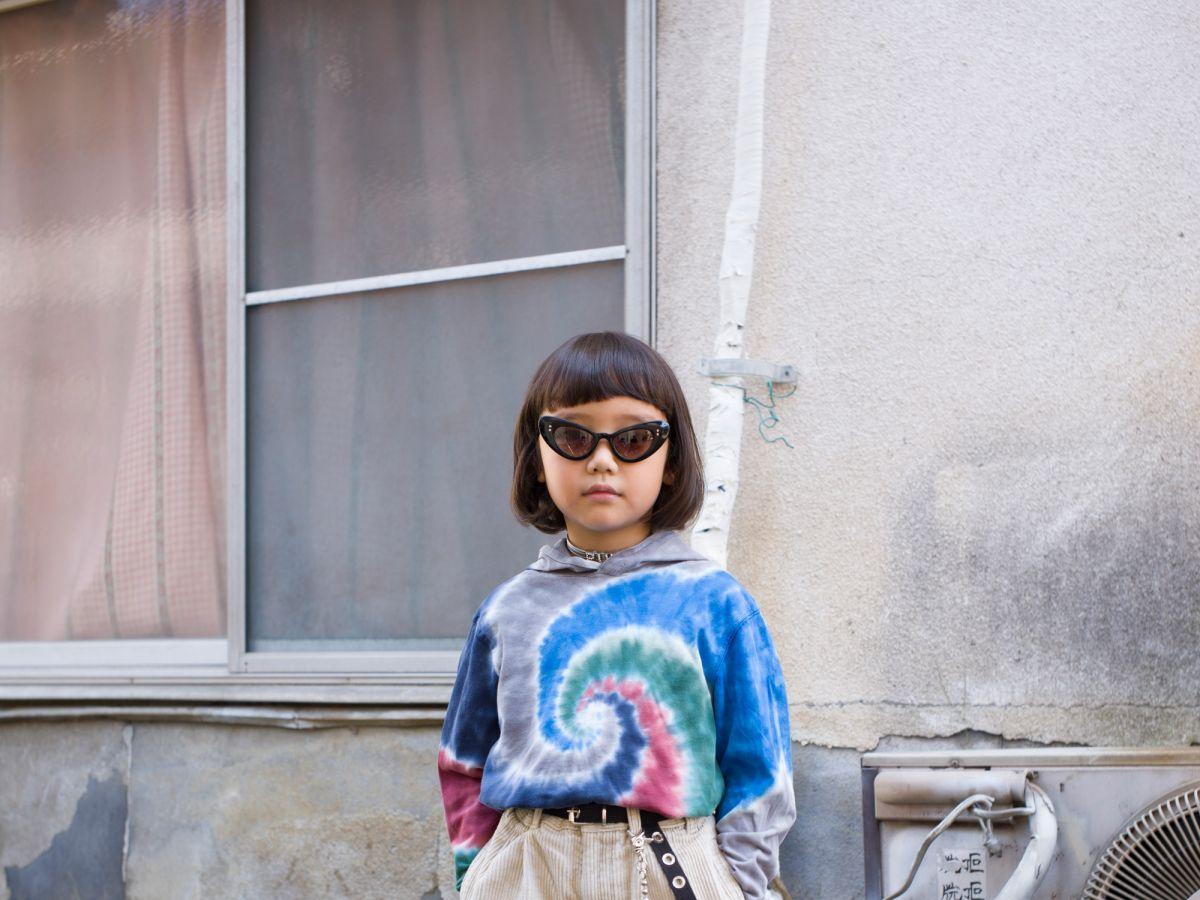 Dziecko, japonka, stojąca w środku kadru, ubrana w okulary przeviwsłoneczne i kolorową bluzkę