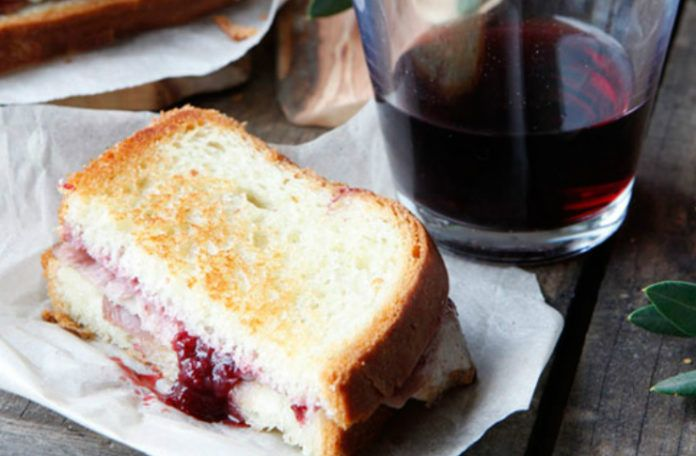 Tost na talerzu, obok szklanka wina