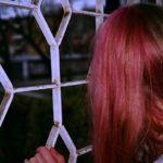 Dziewczyna z różowymi włosami oglądająca coś zza białej kraty