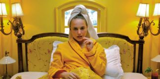 Kobieta leżąca w żółtym łóżku w żółtym pokoju, z ręcznikiem na głowie