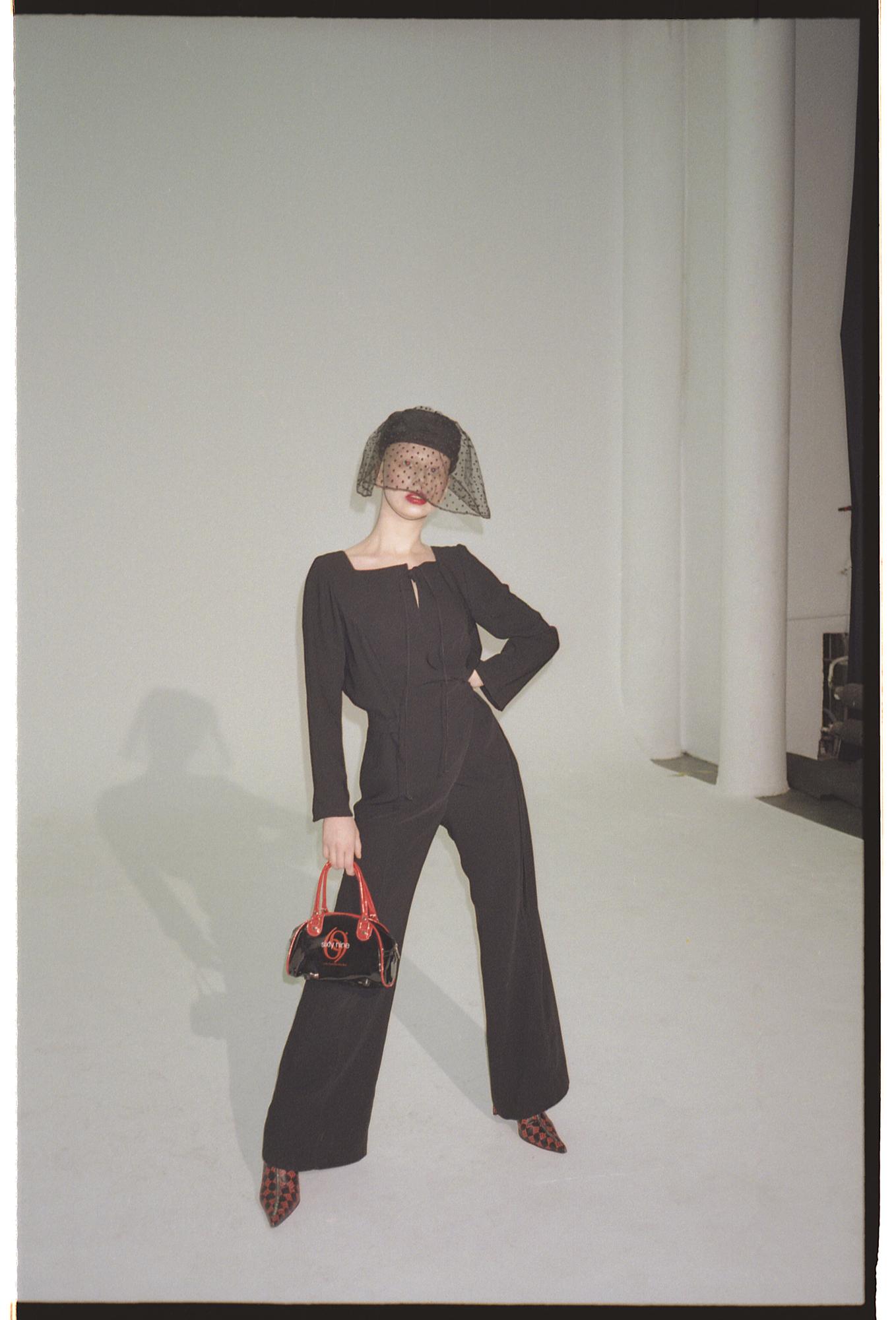 na zdjeciu widzimy lysa kobiete stojaca w rozkroku na tle szarej sciany ubrana na czarno w czarnym toczku z woalka w reku trzyma czarna torebke z czerwonymi uchwytami
