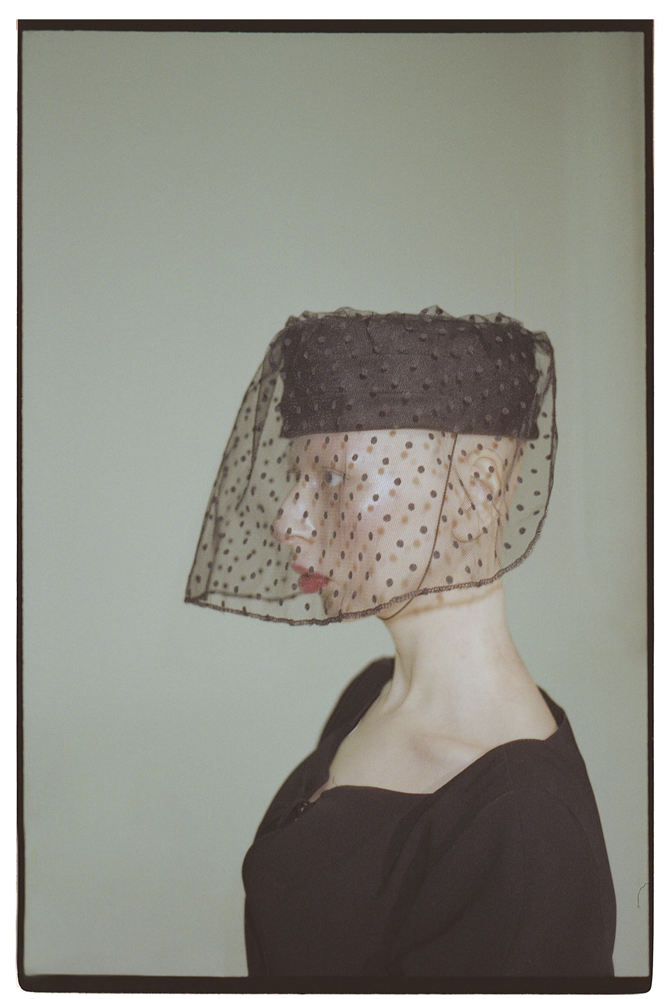 na zdjeciu widzimy lysa kobiete profilem ubrana na czarno w czarnym toczku z woalka zdjecie jest na szarym tle