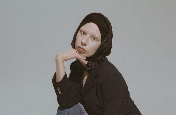 zdjecie przedstawia kobiete w czapce i hustce na glowie ubrana na czarno dlonia podpierajaca podbrudek o smutnym zmyslonym wzroku zdjecie na szarym tle
