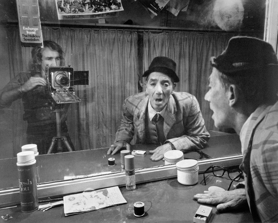 Mężczyzna robiący miny do lustr, obok drugi, robiący mu zdjęcie