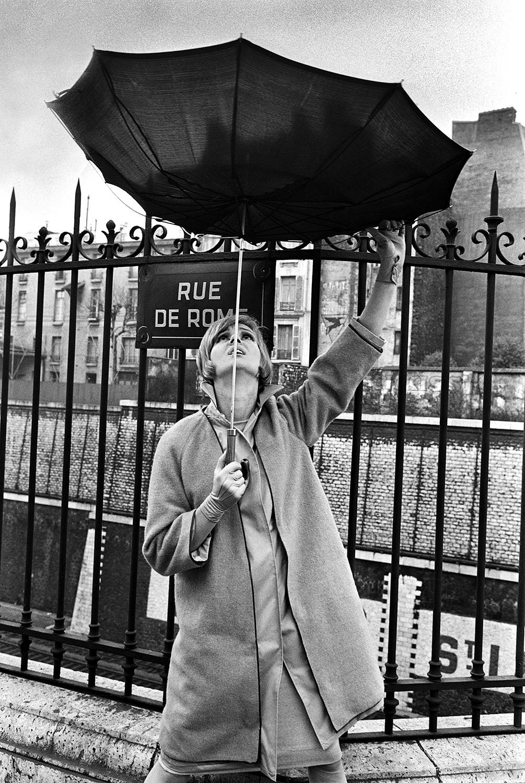 czarno-biale zdjecie kobiety stojacej na ulicy i trzymajacej parasol