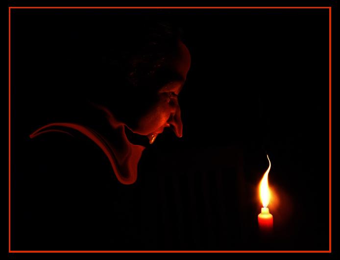 Profil wiedźmy na czarnym tle i patrzącej na płomień świecy