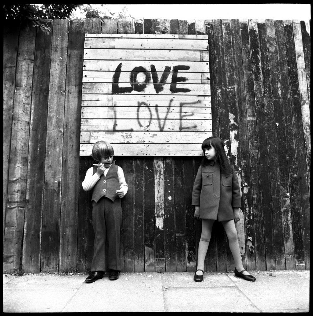 czarno-biale zdjecie dzieci stojacych pod drewnianym plotem z napisem LOVE