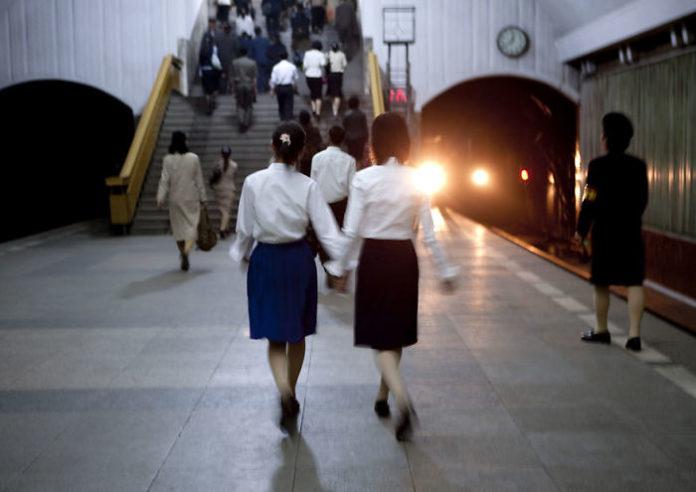 Dwie dziewczyny trzymające się za rękę w metrze